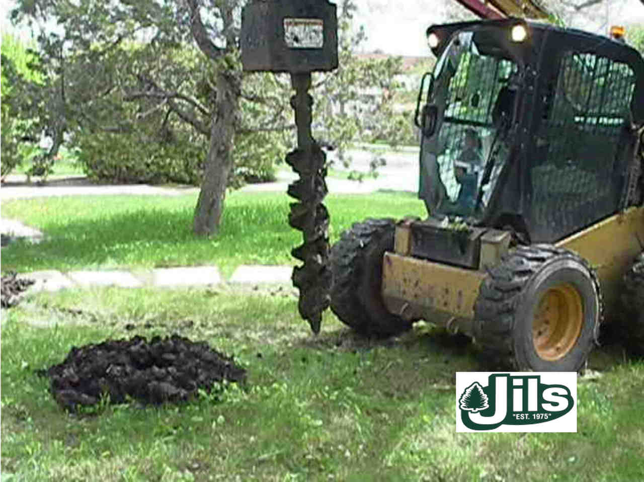Bobcat drilling post hole